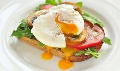 Tostada de huevo escalfado, rúcula, champiñones y tomate