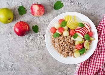Healthy breakfast. Buckwheat or porridge with fresh melon, watermelon, apple and pear. Tasty food. Top view, copy space, flat lay